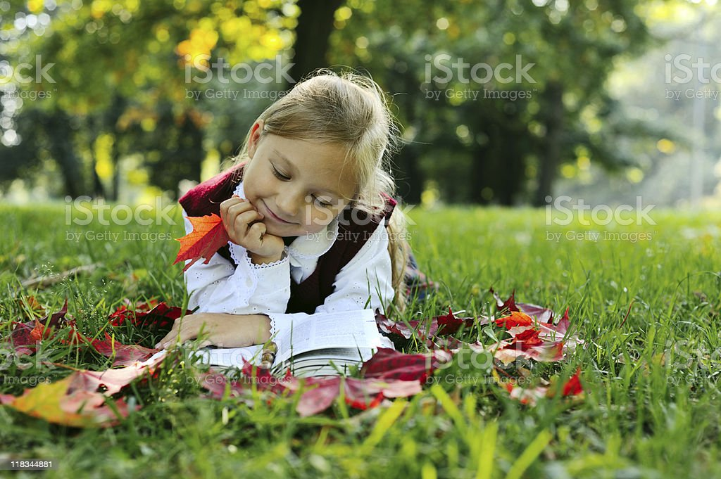 Little schoolgirl laying in the park with book stock photo