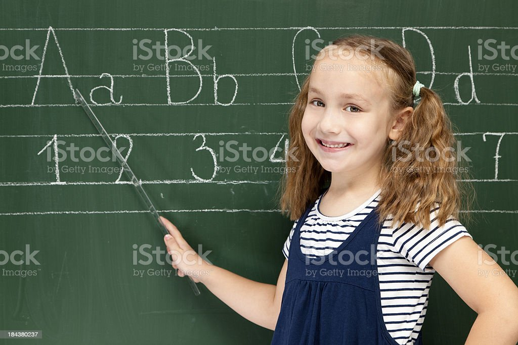 Little schoolgirl writing on chalkboard royalty-free stock photo