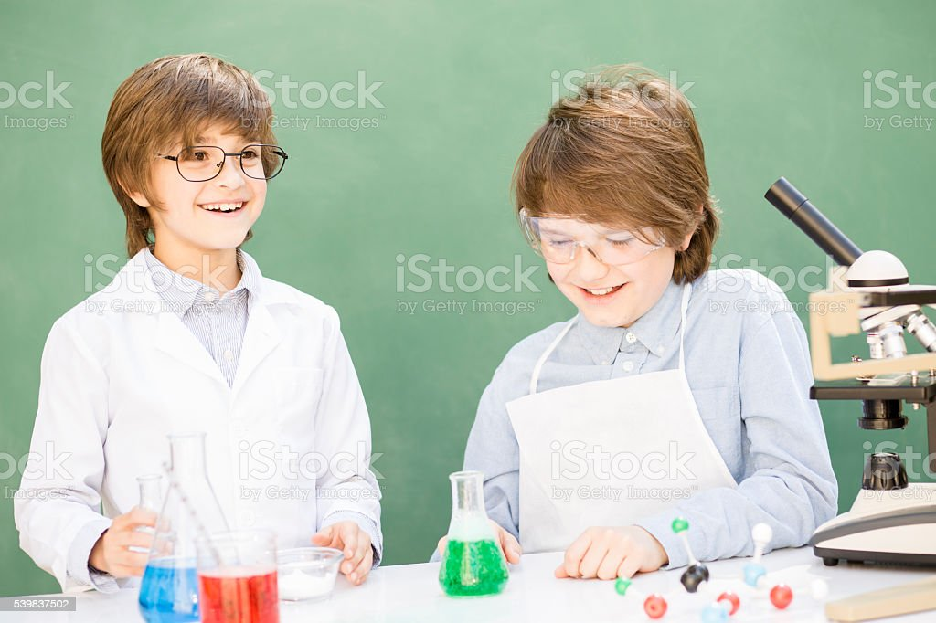 Little scientists! Elementary-age children collaborate on science experiments. stock photo