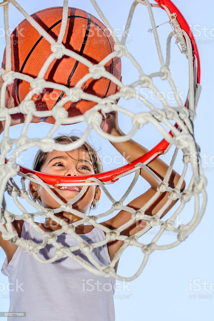 Little seven year old girl playing basketball stock photo