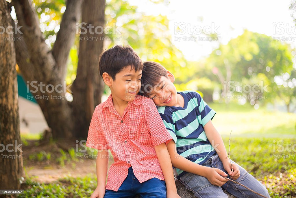 Little sibling boy sitting together in the park stock photo