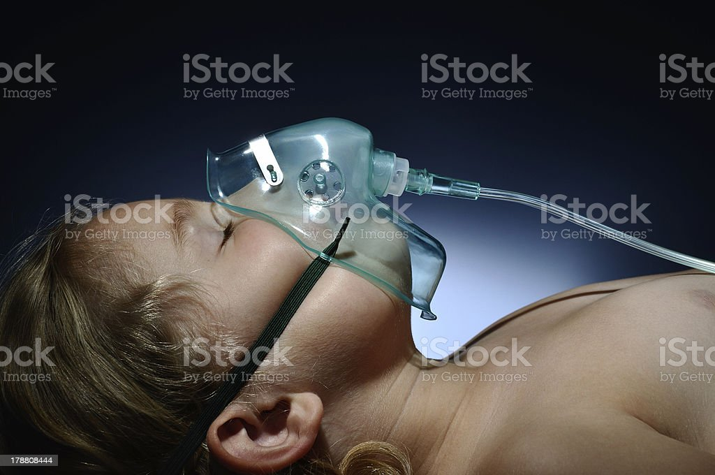 Little, sick girl in mask oxygen. stock photo