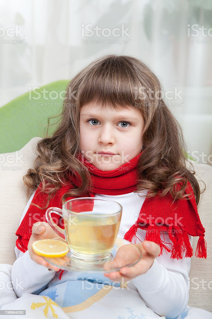 Little sick girl with scarf in bed is taking medicine stock photo