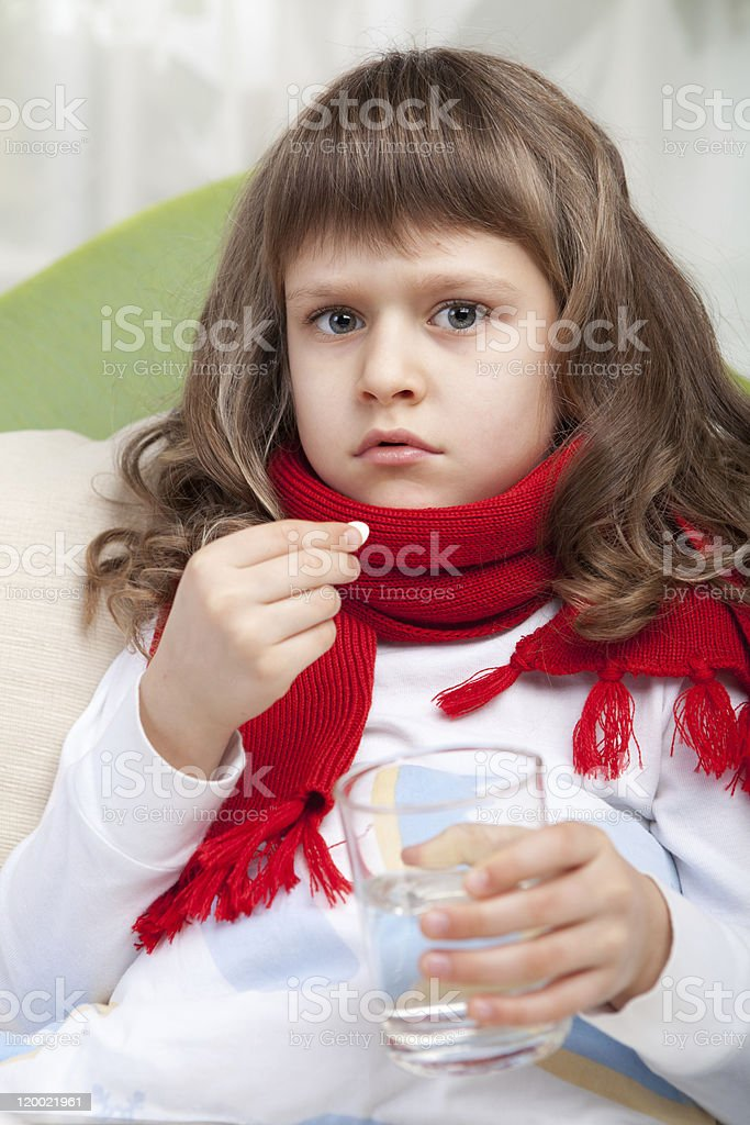 Little sick girl with scarf in bed is taking pill royalty-free stock photo