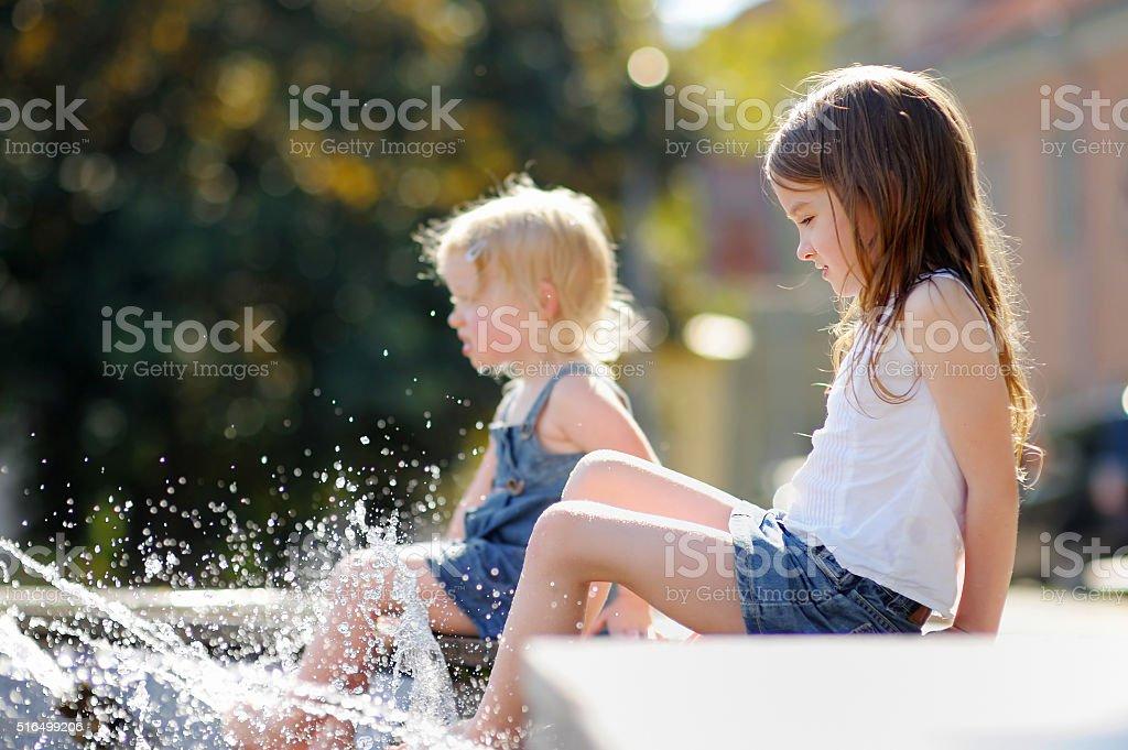 Little sisters having fun in a fountain stock photo