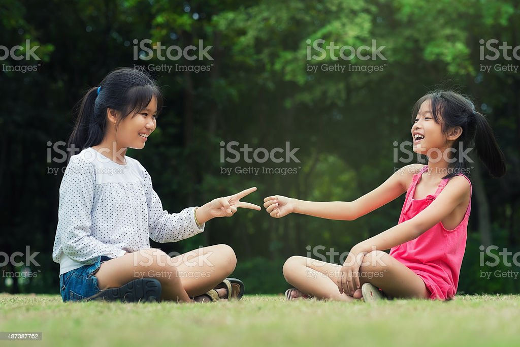 Little sisters is Rock-Paper-Scisors for fun stock photo