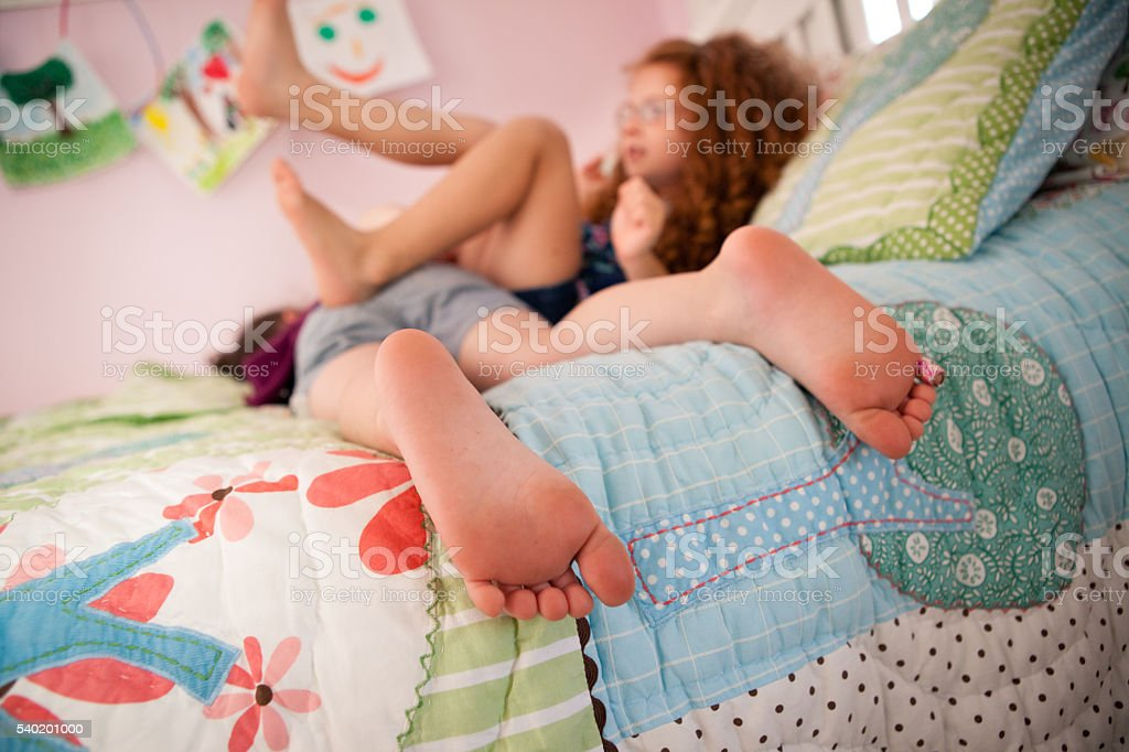 Little Sisters Playing Together on Bed in Bedroom stock photo