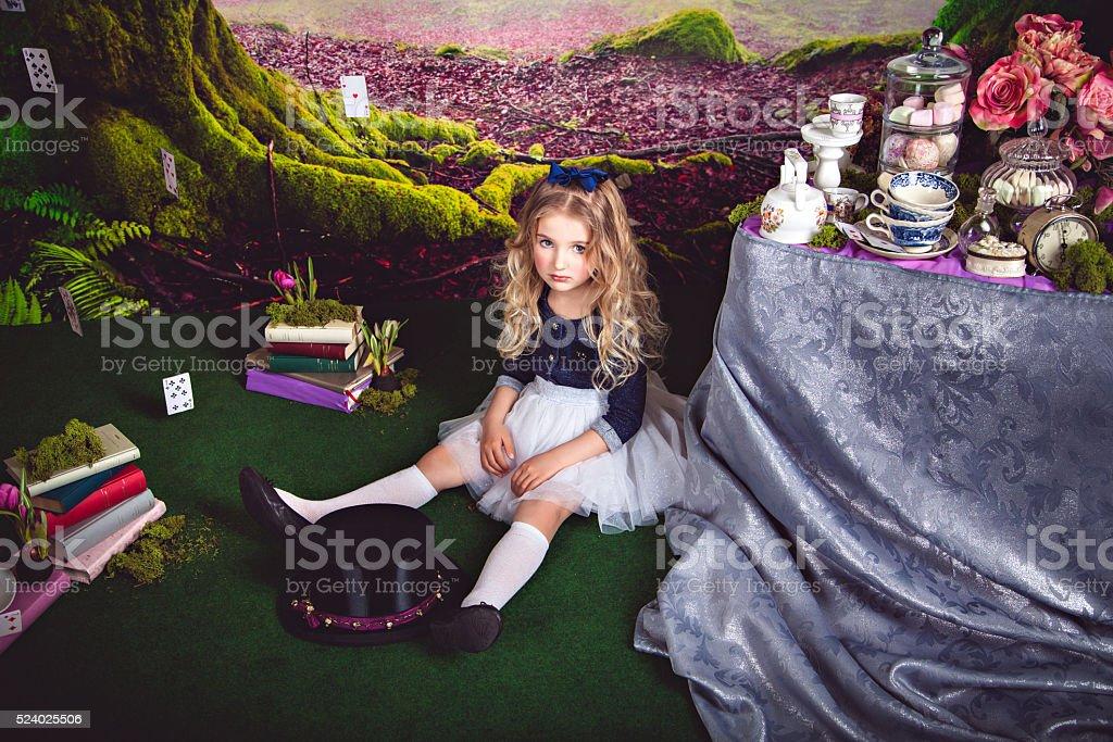 Little sitting on the floor girl as Alice in Wonderland stock photo