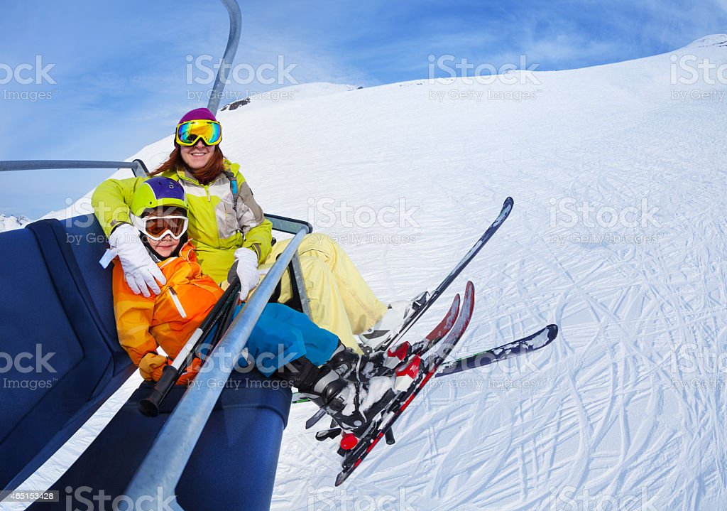 Little skier boy with mother lift on mountain stock photo