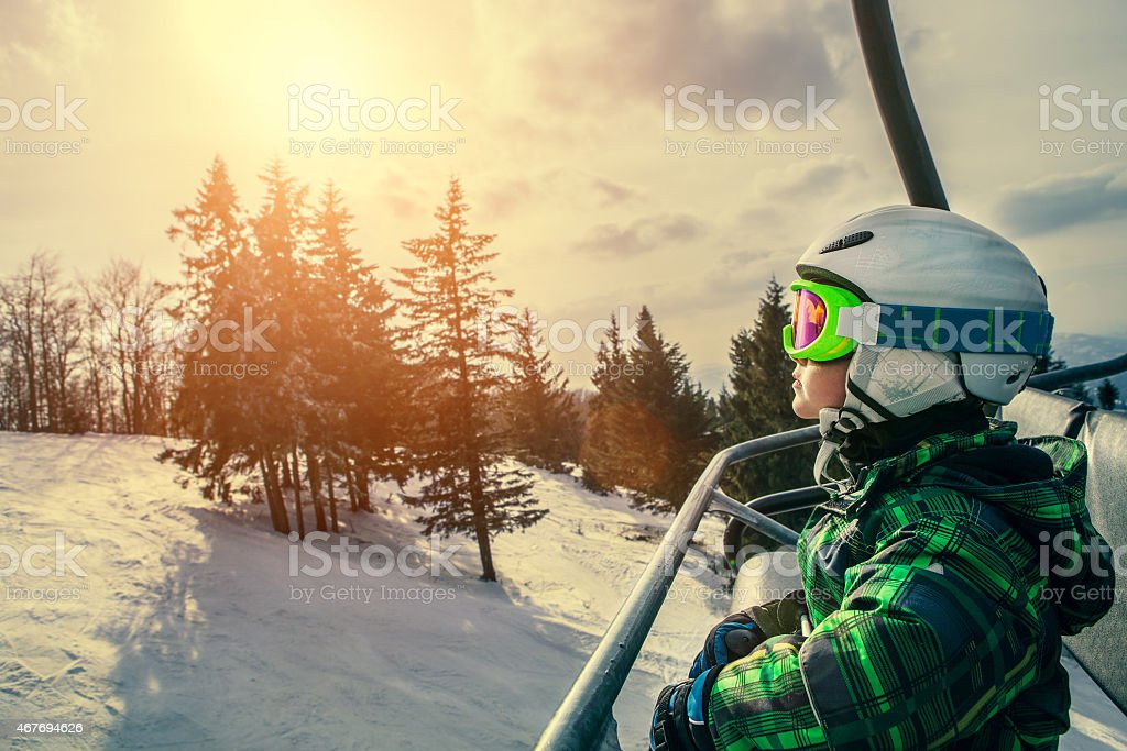 Little skier on the ski lift stock photo