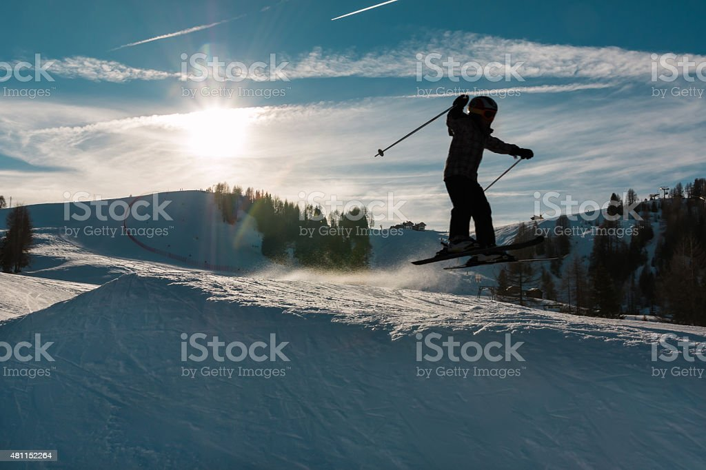 Little skier performs jump in the snow stock photo