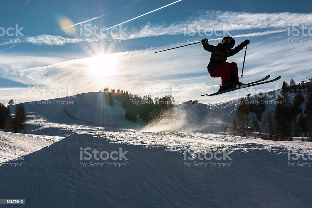 Little skier performs jump in the snow, silhouette stock photo