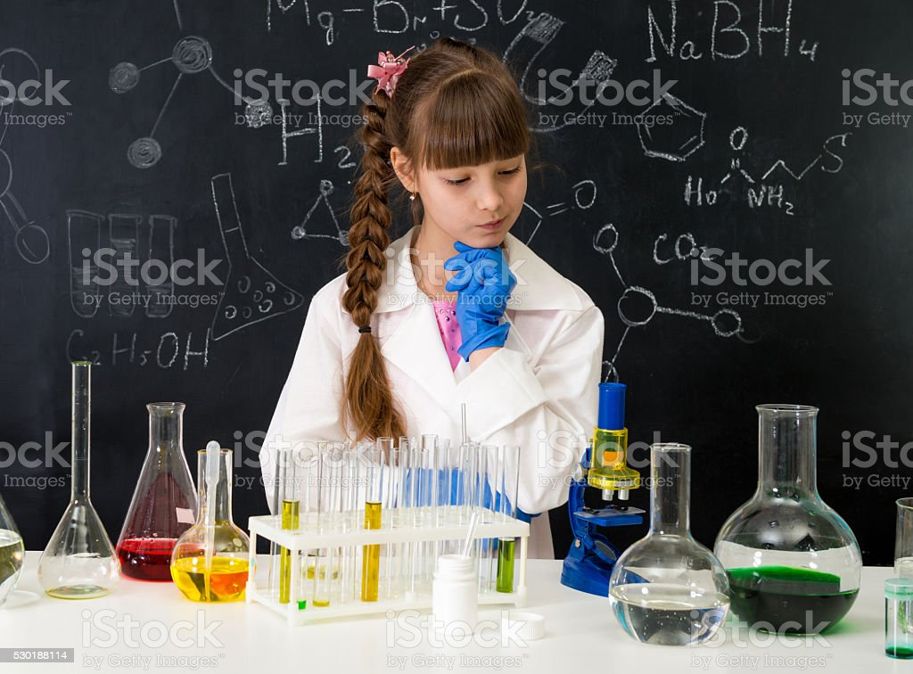 little smarl girl in chemistry lab doing an experiment stock photo