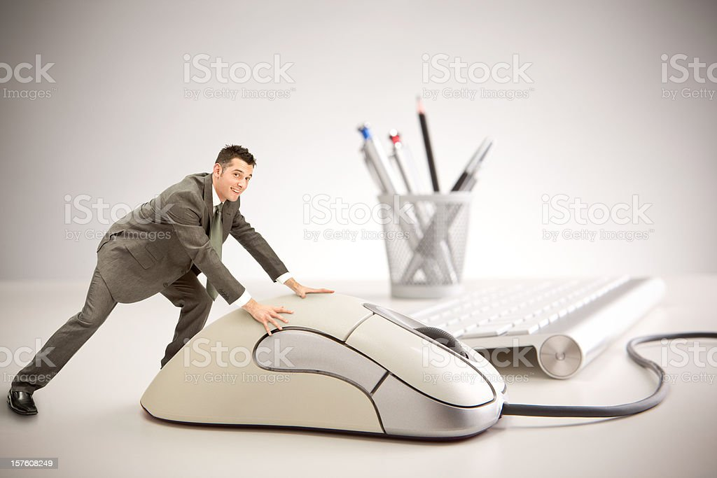 Little smiling business man using giant mouse at work royalty-free stock photo