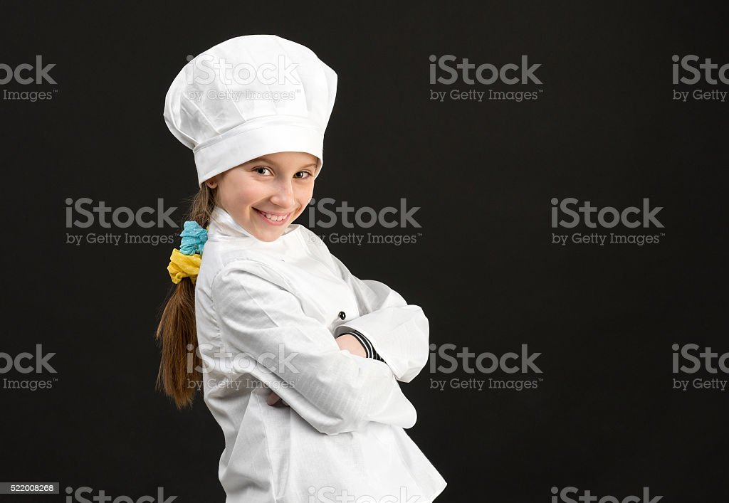 little smiling girl in white chef costume stock photo