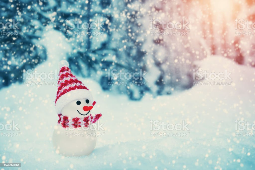 little snowman on soft snow in the forest stock photo