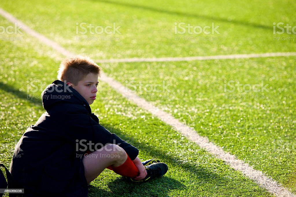 little soccer player expelled sad sitting on the sideline stock photo