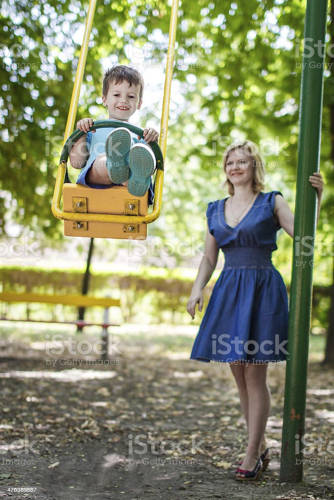 Little son swing with mother at park royalty-free stock photo