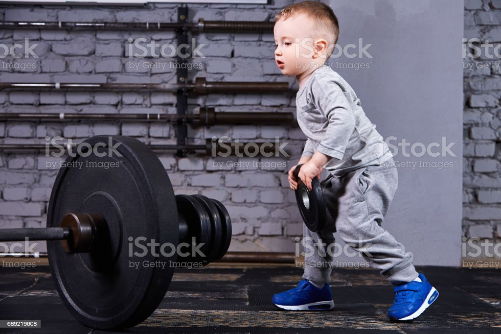 Little sporty child with barbbell against brick wall at the    gym. stock photo