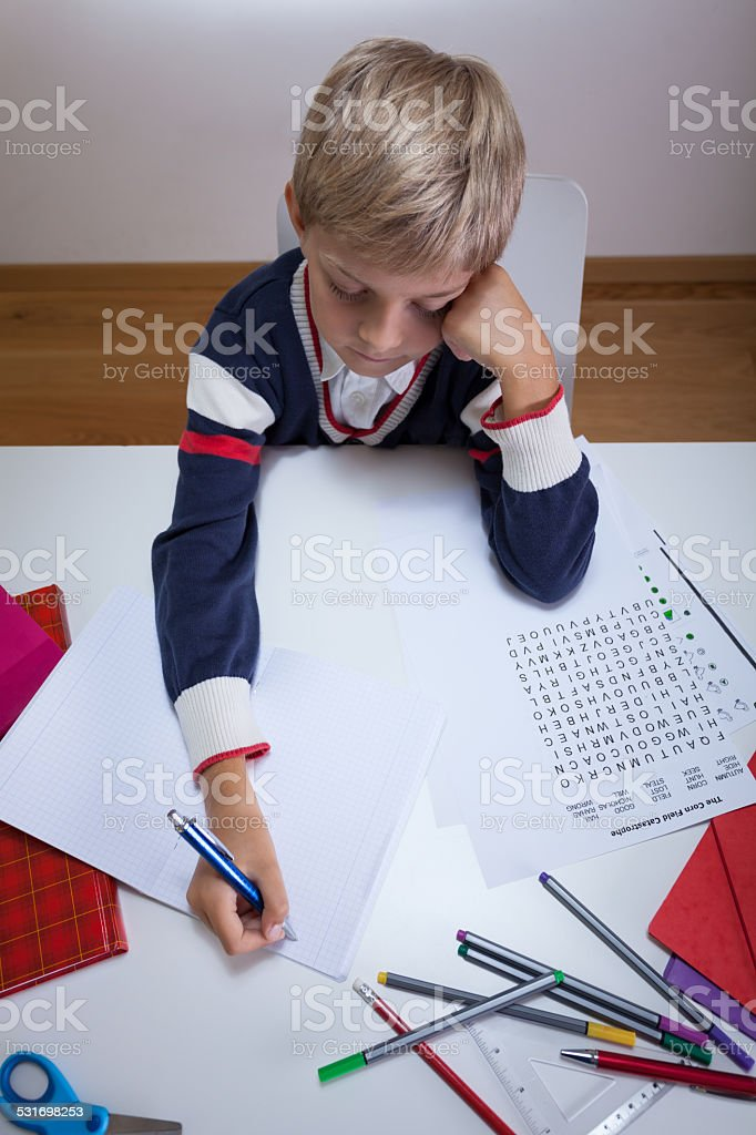 Little student writing in notebook stock photo