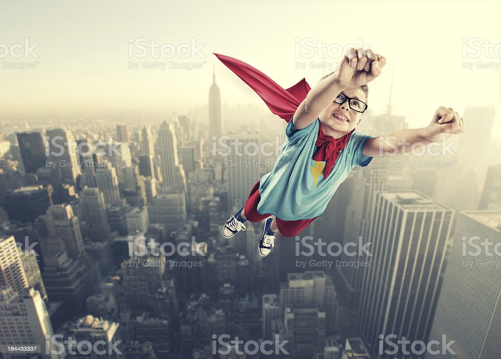 Little superhero boy flying in the air stock photo