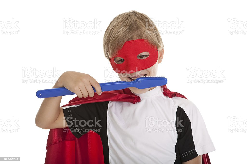 Little Superhero Brushing Teeth with Large Toothbrush stock photo