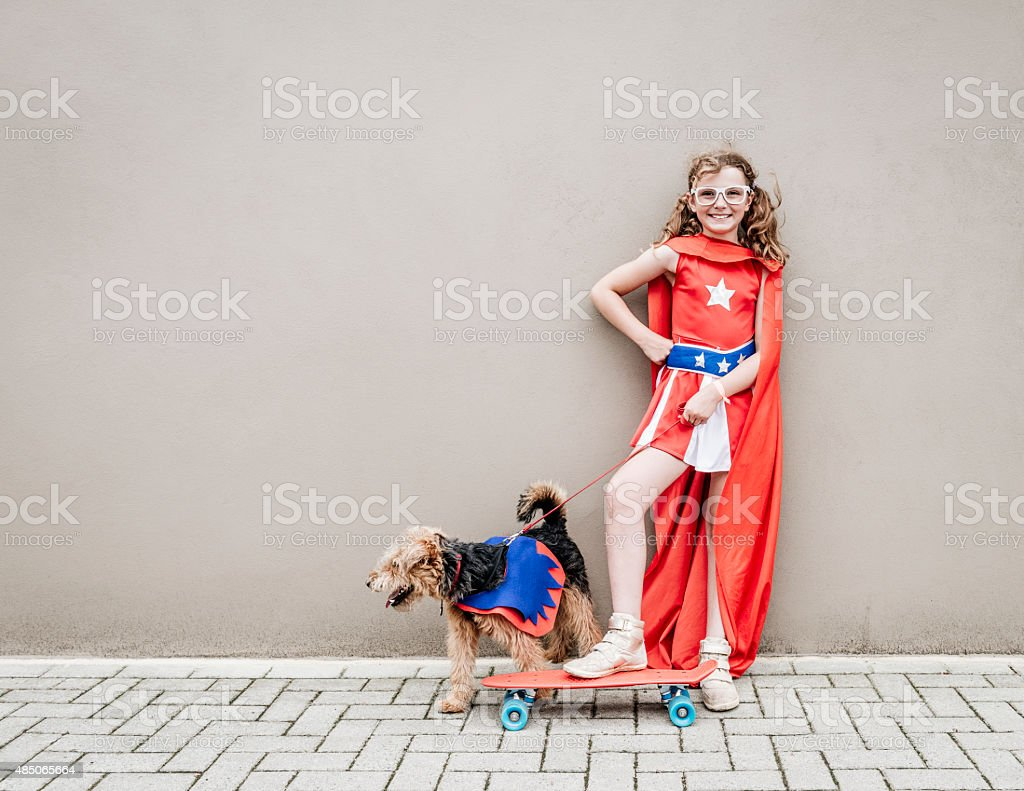 Little superhero girl with her dog and skateboard stock photo