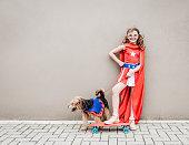 Little superhero girl with her dog and skateboard