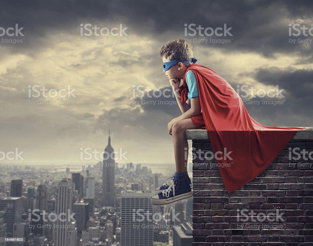 Little superhero sitting on top of wall stock photo