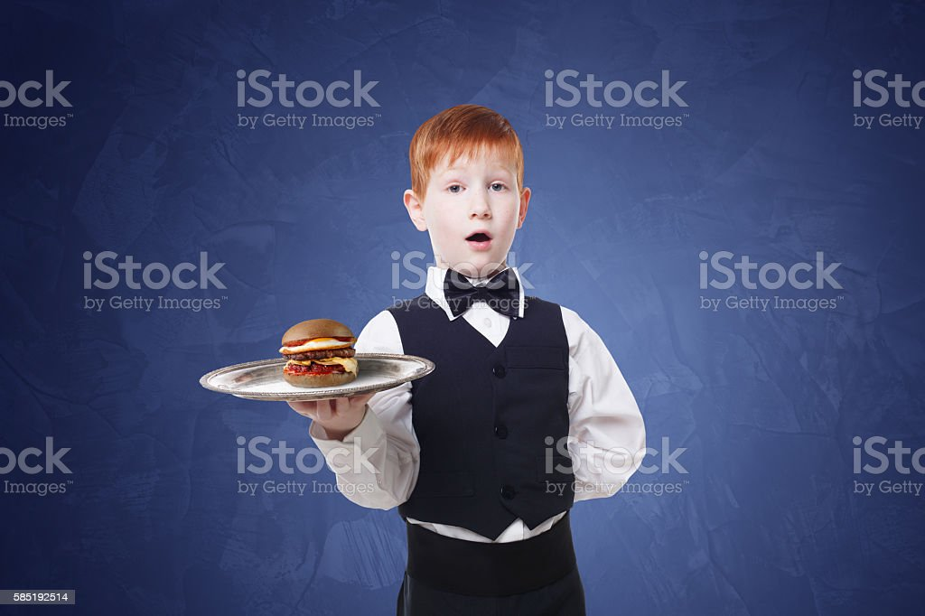 Little surprised boy waiter stands with tray serving hamburger stock photo
