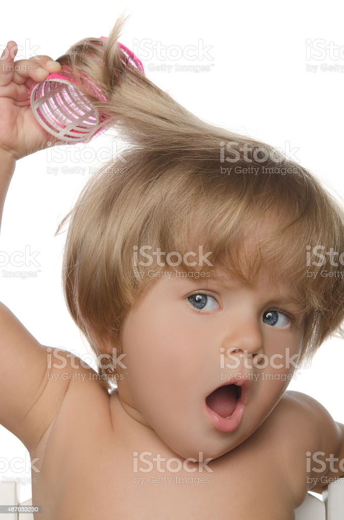Little surprised girl with hair curlers stock photo