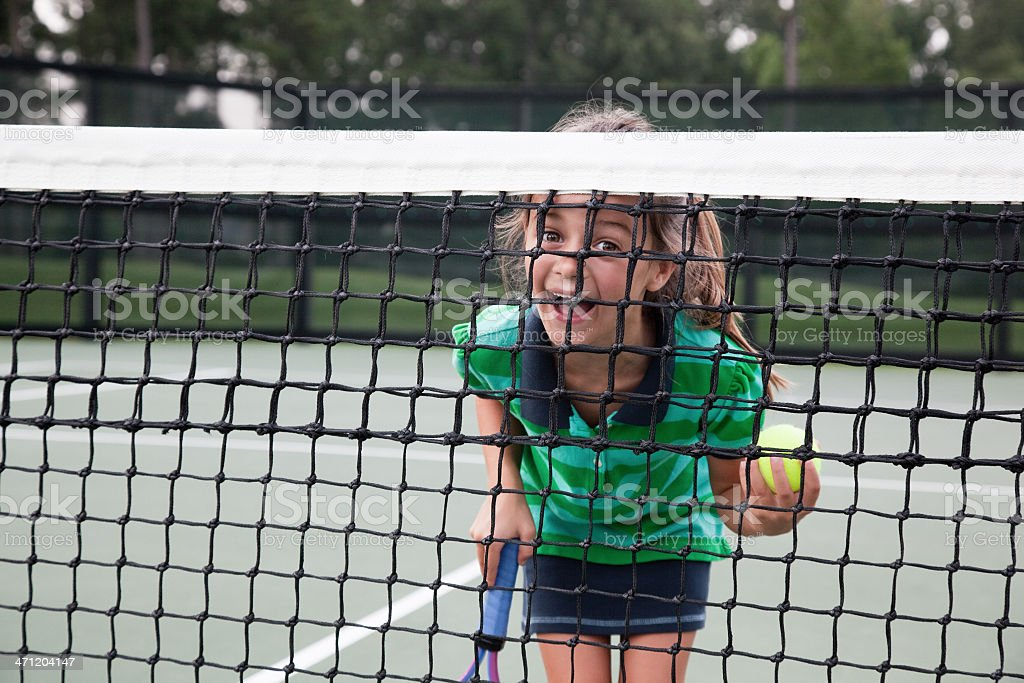Little Tennis Player Smiling behind Net stock photo