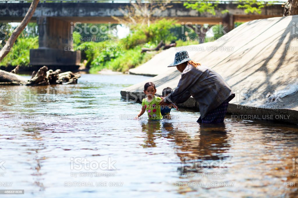 Little Thai girl and senior woman in river Phetchaburi stock photo