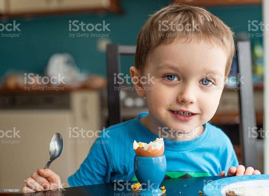 Little three year old boy eats an egg stock photo