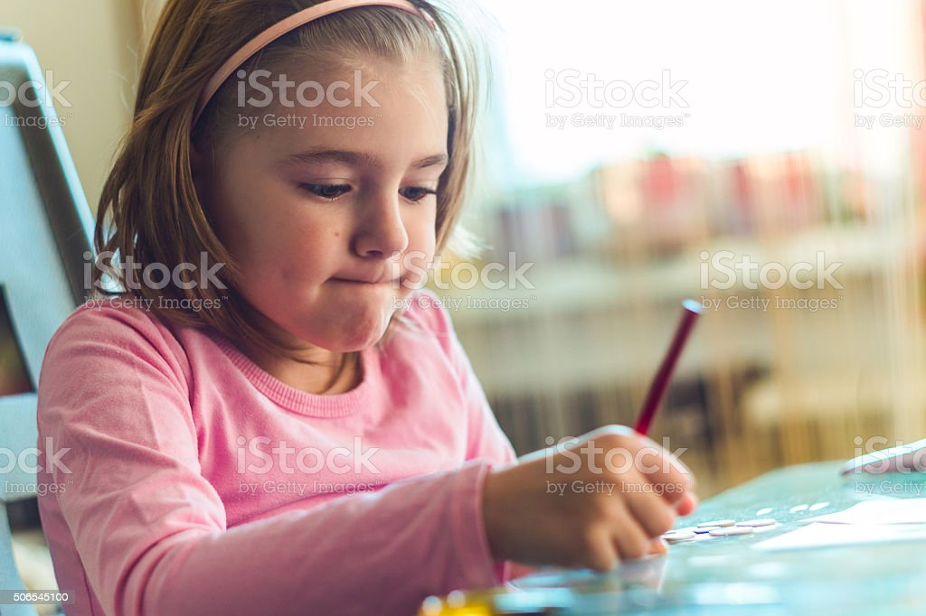 little tired girl sitting at the desk stock photo