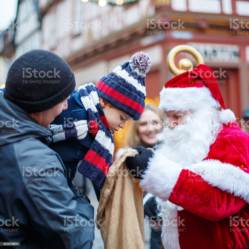 Little toddler boy,  father and Santa Claus on Christmas market stock photo