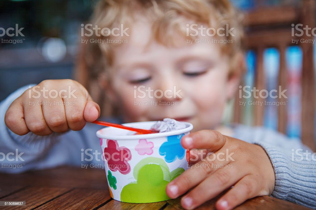 Little toddler eating ice cream summer stock photo