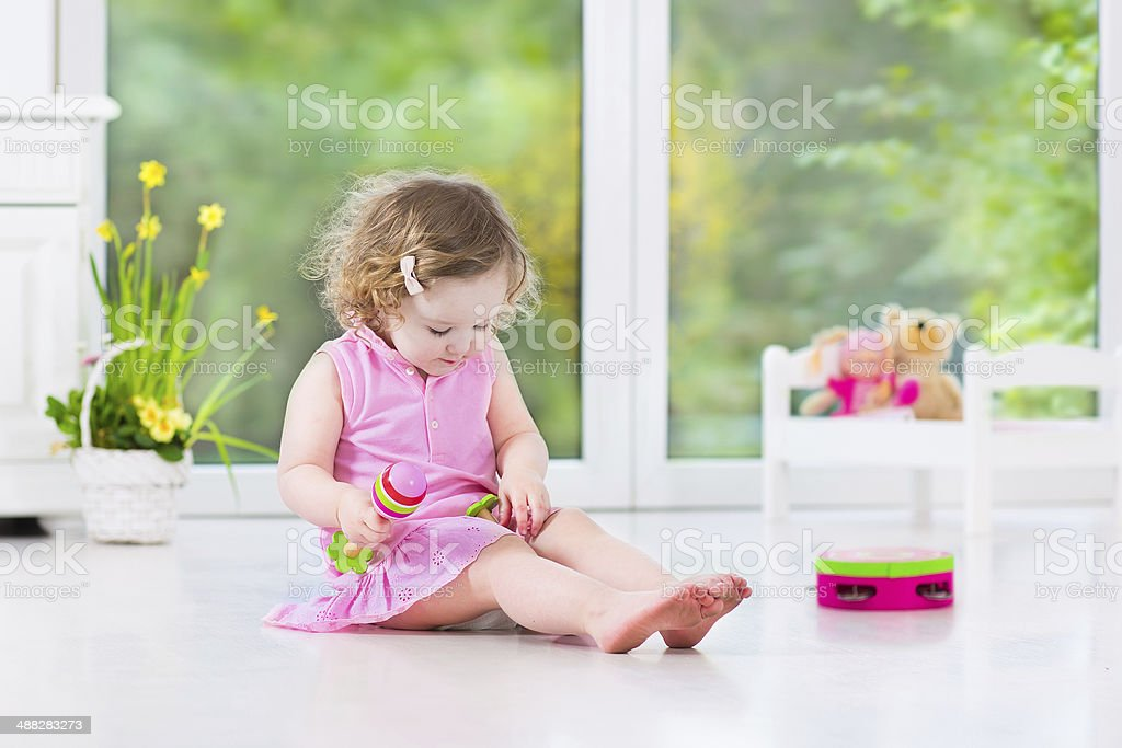 Little toddler girl playing tambourine in sunny white room stock photo