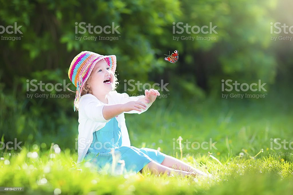 Little toddler girl playing with butterfly stock photo