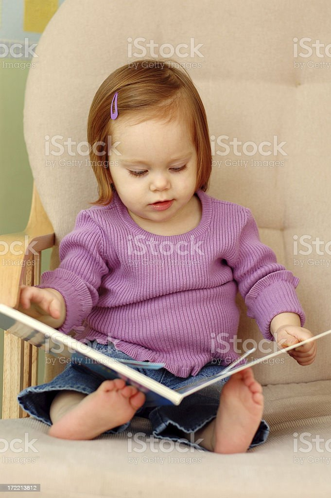 Little Toddler Girl Sitting in Chair Reading a Book royalty-free stock photo
