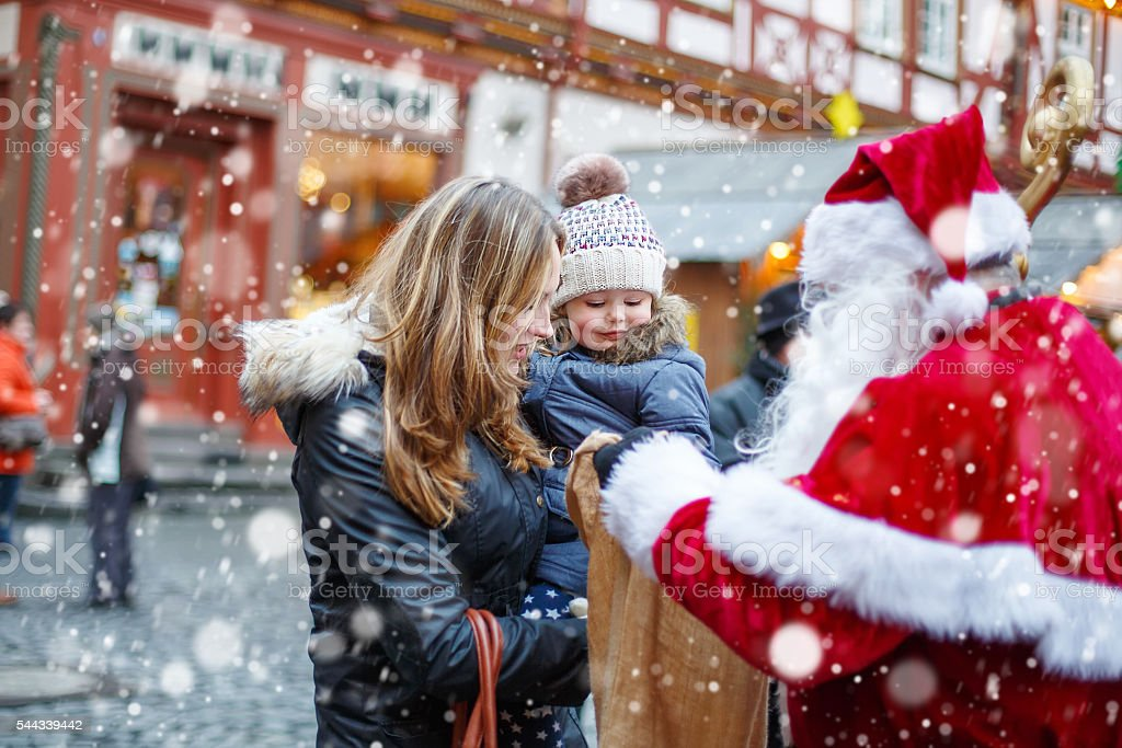 Little toddler girl with mother on Christmas market. stock photo