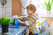 Little toddler helping in kitchen with washing dishes
