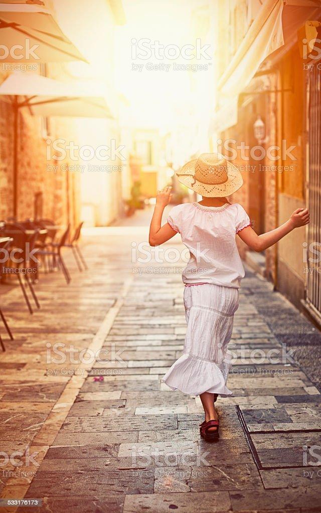 Little tourist girl visiting mediterranean town. stock photo