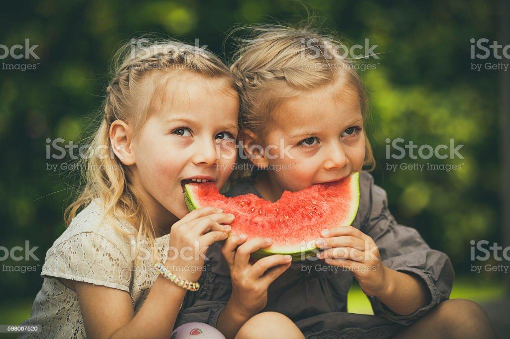 little twin girls eating melon stock photo