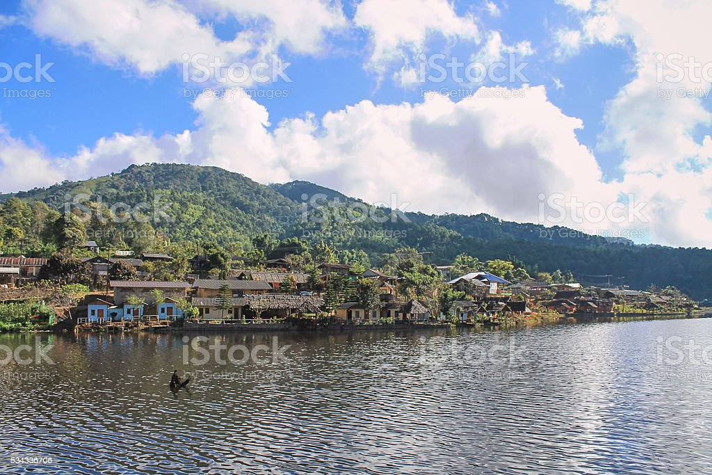 Little village in the valley, is situated near the beautiful lake. stock photo