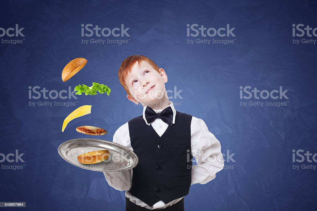 Little waiter stands with tray serving hamburger separate flying toppings stock photo