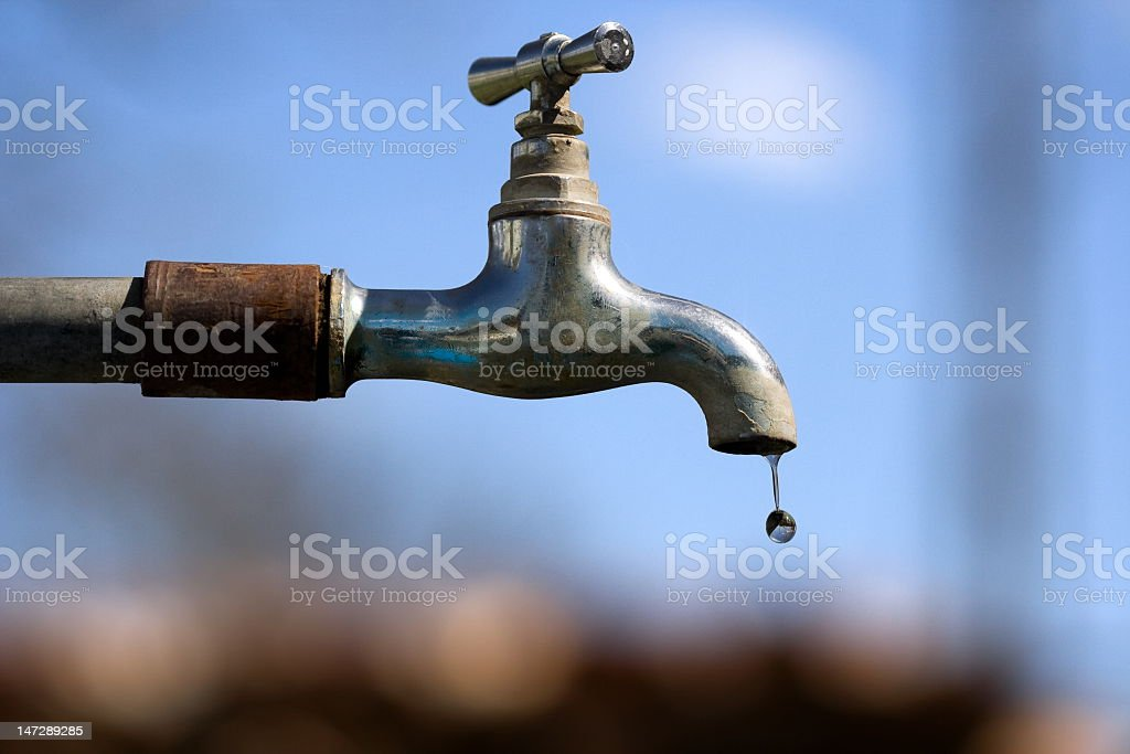 A little water droplet falling from the garden tap stock photo