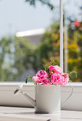 Little white watering can with roses bouquet near the window