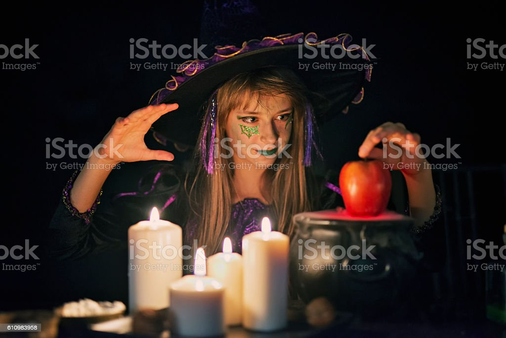 Little witch preparing poisoned apple stock photo