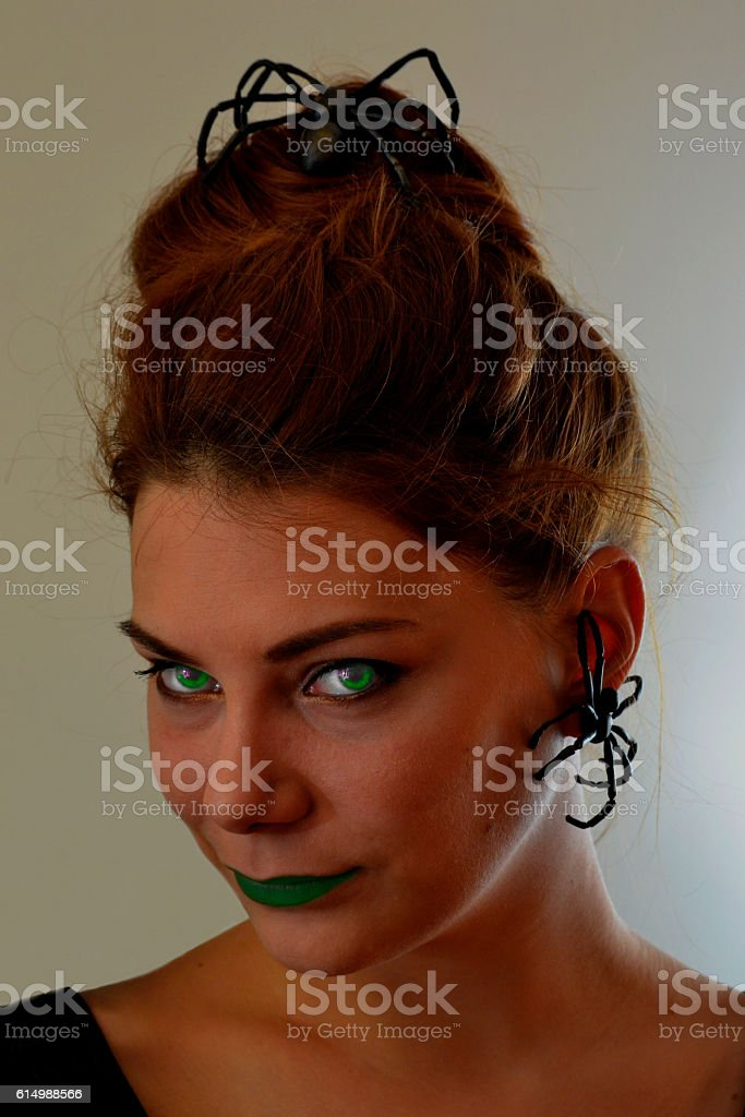Little witch with green eyes and lips stock photo